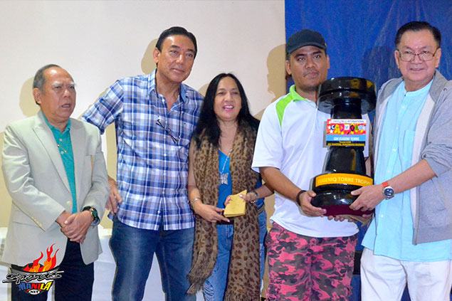 "FIDE Master David Elorta happily receives the ""Eugene Torre Trophy"" from Chess Circle Club International founding head/ president Leonardo ""Nards"" Jimenez and vice president Exy Perez after topping the Chess Circle Club-All Masters Rapid chess at the Activity Hall of Alphaland Makati Place in Makati City. Also in photo are event coordinator si Lea Bautista and NCFP Executive Director Red Dumuk."
