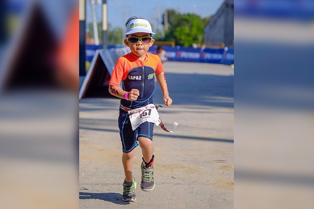 Six-year-old Damien Palo Lapaz jogs to the finish line as he completes the run part of his event. Karen Padawag